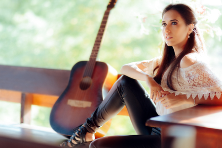 Portrait of a Beautiful Woman next to Her Guitar