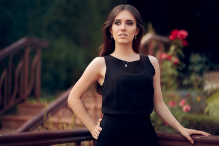 Elegant Woman Wearing Black Dress Standing in a Patio Stock Photo