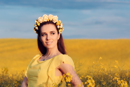 Summer Woman with Roses Wreath in a Field of Flowers Stock Photo