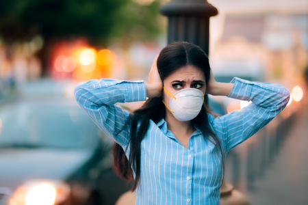 Girl With Mask Covering her Ears Because of Noise Pollution Stock Photo