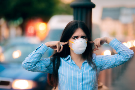 respiration: Girl With Mask Covering her Ears Because of Noise Pollution Stock Photo