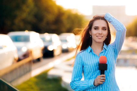 live work city: Female News Reporter on Field in Traffic Stock Photo