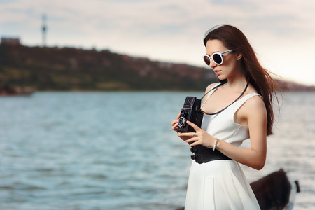 Retro Woman with Vintage Photo Camera on a Beach Stock Photo
