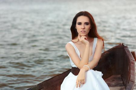 Femme réfléchie en robe blanche assise dans un vieux bateau Banque d'images - 80597649