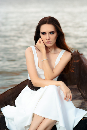 Sad Woman in White Dress Sitting in an Old Boat Stock Photo