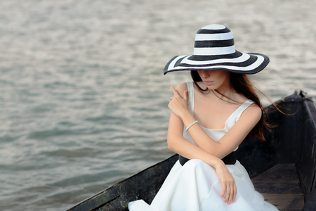 Mysterious  Woman in White Dress Sitting in an Old Boat Stock Photo