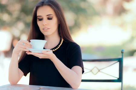 caffeine free: Beautiful Woman with Statement Necklace Having a Cup of Coffee Stock Photo