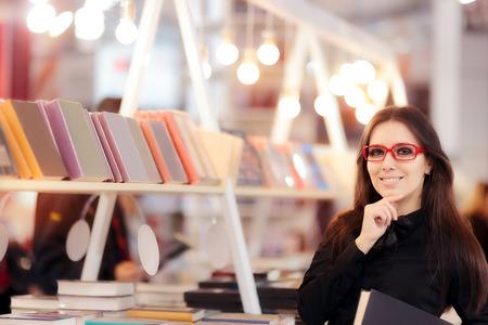 책장 앞에 책을 들고 웃는 소녀 스톡 콘텐츠