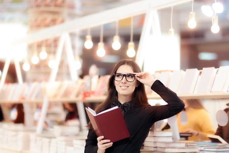 Smiling Girl Holding a Book in front of a Bookshelf