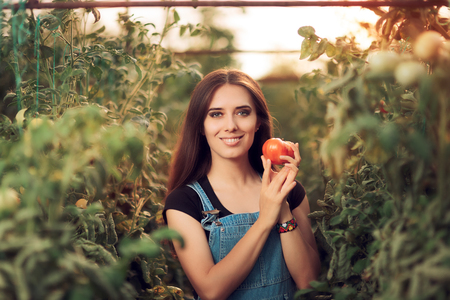 Happy Farm Girl Holding a Tomato inside a Greenhouse