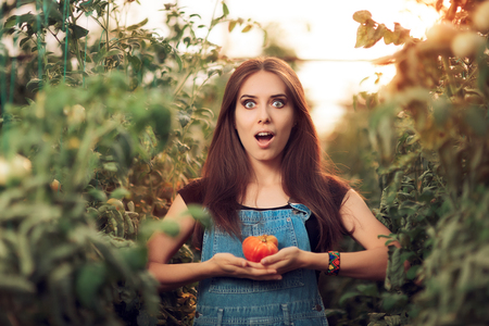 Surprised Farm Girl Holding a Tomato inside a Greenhouse