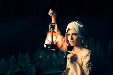 Curious Medieval Woman with Vintage Lantern Outside at Night Banco de Imagens
