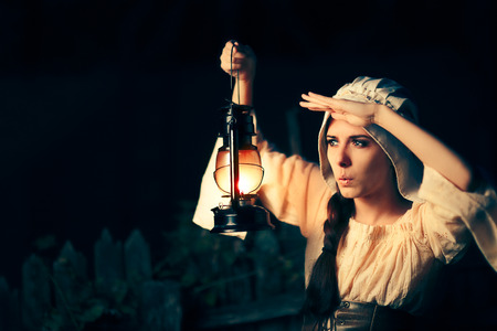 Curious Medieval Woman with Vintage Lantern Outside at Night Stock Photo