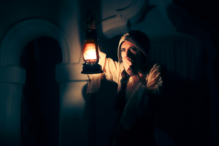 Scared Medieval Woman with Vintage Lantern Outside at Night