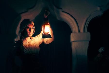 중세 여성이 밤에 외부의 빈티지 랜턴으로