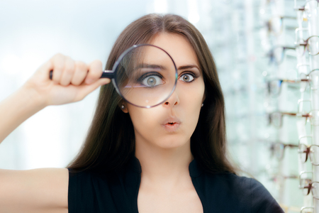 Funny Woman with Magnifying Glass Ready For Eye Exam Stock Photo