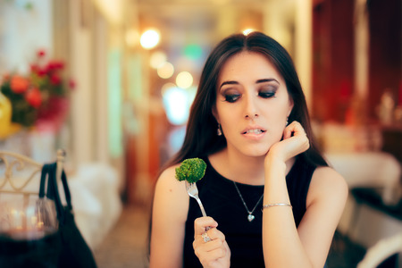 Funny Woman Eating Broccoli At a Party Stockfoto