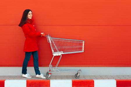 Mujer con carro listo para ir de compras en temporada de vacaciones Foto de archivo
