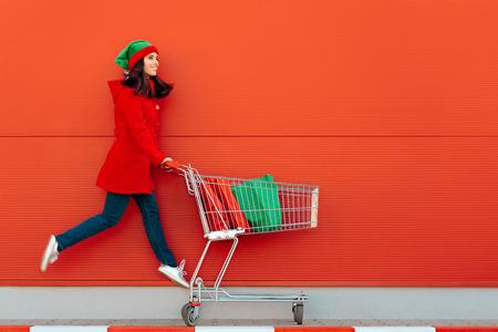 Mujer feliz con carrito de la compra listo para la venta de Navidad Foto de archivo