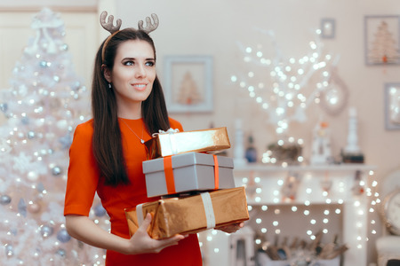 Cheerful Woman with Many Christmas Presents in Decorated Home