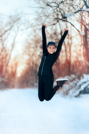 Happy Girl in Sportswear Outfit Jumping in the Snow