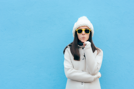 Funny Woman with Yellow Sunglasses Thinking on Blue Background