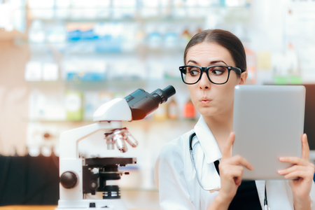 Scientist with Microscope and Pc Tablet doing Research Study