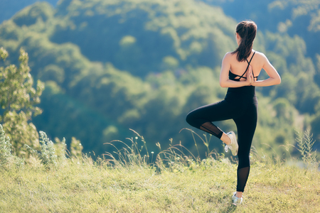 Fitness Woman Exercising Flexibility and Balance in Beautiful Nature