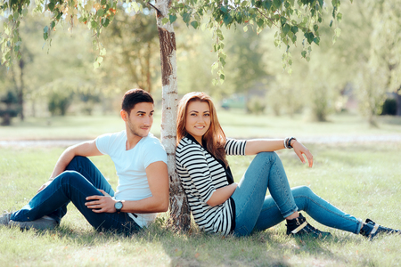Happy Couple in Love Sitting Under a Tree in the Park Stock Photo