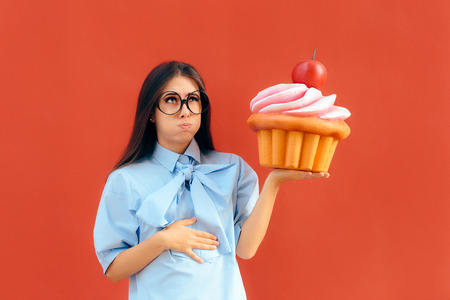 Donna che soffre di mal di stomaco dopo aver mangiato troppo Cupcake Archivio Fotografico - 93476667