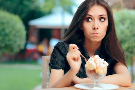 Girl Heisting to a Eat High Calorie Ice Cream Dessert Stockfoto