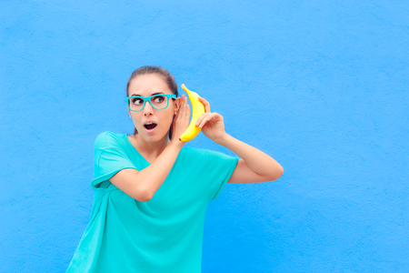 Funny Girl with Eyeglasses and Banana Phone on Blue Background