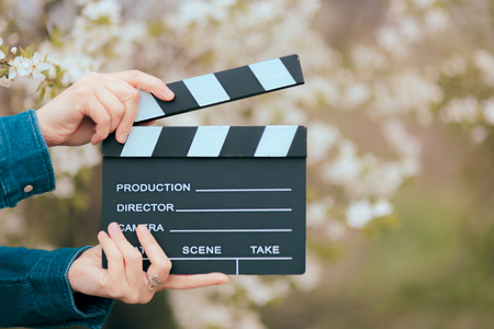 Hands Holding Film Slate Cinema Clapper on Spring Blooming Background Archivio Fotografico