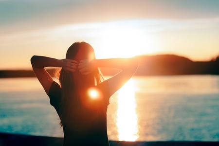 Szczęśliwa kobieta z nadzieją, patrząc na zachód słońca nad morzem Zdjęcie Seryjne