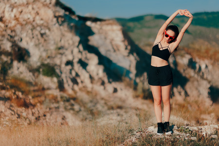 Woman Stretching Ready To Work Out Outdoors on Mountains Stock Photo