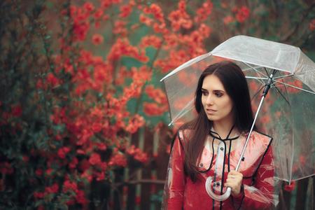 Beautiful Woman with Transparent Raincoat and Umbrella Enjoying Rain