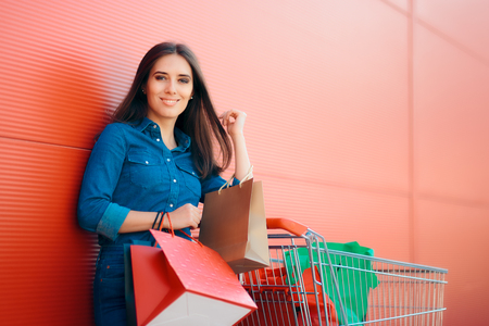 Happy Shopper Woman with Shopping Cart in front of Store Stock Photo