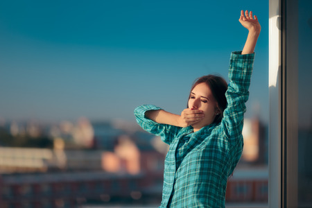 Sleepy Morning Woman in Pajamas Yawning in The Balcony Stock Photo