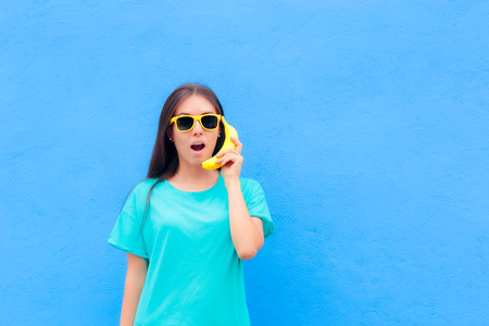 Funny Girl with Sunglasses and Banana Phone on Blue Background Stock Photo