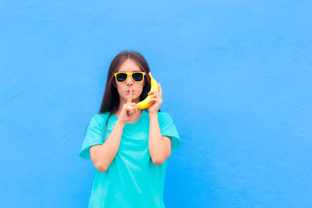 Funny Girl with Sunglasses and Banana Phone on Blue Background 免版税图像