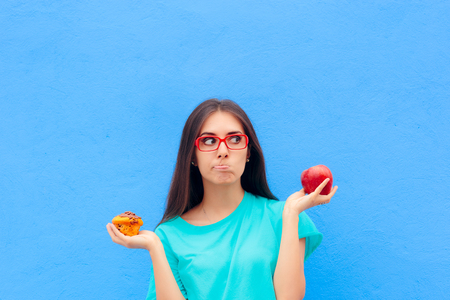 Woman Choosing Between Unhealthy Muffin and Healthy Apple