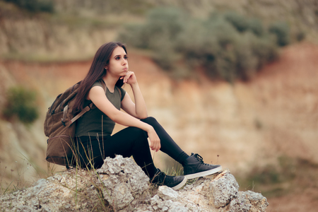Tired Woman Sitting on a Rocky Cliff Stock Photo