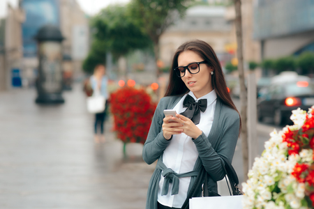 Woman with Smartphone and Shopping Bag Walking on the Street