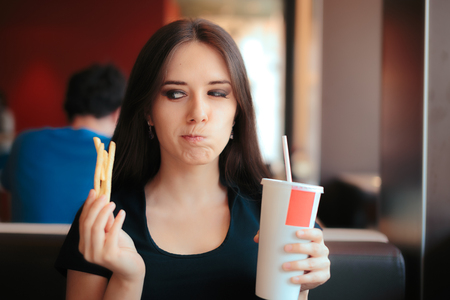Hesitating Woman Thinking about Eating Fast Food or Not Stock Photo