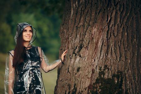 Trendy Woman in Clear Transparent Raincoat in Summer Rain