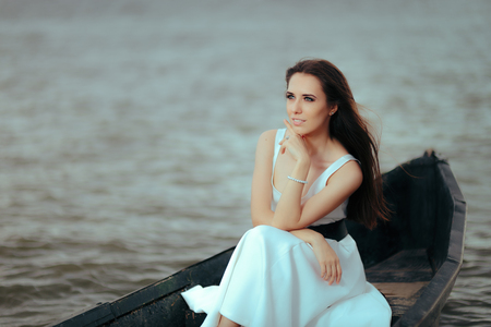 Beautiful lonely woman in old fishing boat floating on sea Stock Photo