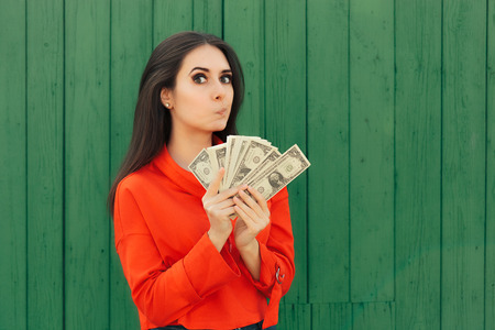 Funny Casual Girl Holding Money Thinking to Invest