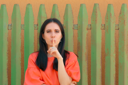 Portrait of a Woman with Finger on her Lips Keeping Secrets Stock Photo