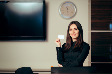 Receptionist Woman in front of Her Desk Greeting Customers Фото со стока