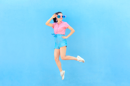 Funny Fashion Girl with Oversized Sunglasses and Jumping